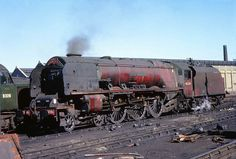 """46246 'City of Manchester'. Coronation Class 4-6-2. LMS Stanier Pacific 46246 """"City of Manchester"""" will not be riding along in the breeze for much longer after this September 1962 shot was taken at Camden MPD.Photo by Captain Tower."""