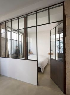 Loft in Paris by Maxime Jansens (15) bedroom with glass wall and large door