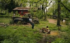 Children playing with a broken toy wagon by their primitive shack in rural Pattison, Mississippi. Pattison is a very poor unincorporated village with high poverty and underprivileged African-American population. The tumbledown shack is not much better than days of slaves and sharecroppers. A derelict pickup truck rusts nearby. 1973