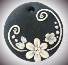 Polymer clay pendant, handmade with applique technique, one of a kind.Black with pearly white flowers, swirls leaves and dots. By Lis Shteindel.