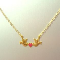 """Love Doves Charm Bracelet Material: Gold/pink enamel. Chain is gold plated with pink enamel. Measures 1"""" wide, 1/2"""" tall. Chain is 16"""" plus 2"""" extension. This is A Skinny by Jessica Elliot piece. Made in the USA. Jessica Elliot Jewelry Necklaces"""