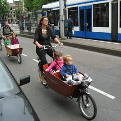 It's called a Bakfiet.  A cargo bike that has space for the groceries and the little people all together.