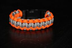 Paracord Survival Bracelet with plastic clip made from 550 paracord in orange and grey.    Pattern is Cobra.    Available in 6, 7 , and 8 inches.