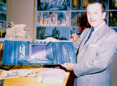 Walt Disney going over one of the pieces of background art for Sleeping Beauty