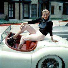 Anita Ekberg sitting on the trunk of her convertible Jaguar, photo by Gene Lester, Hollywood, California c. 1955