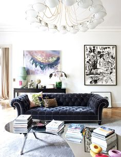 Living room with blue velvet tufted sofa and vintage brass ceiling lights