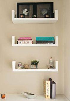 Ao lado da TV, o trio de prateleiras que integra o projeto do rack expõe livros, álbuns de fotos e objetos decorativos. A dupla de quadros escuros sai por R$ 39,90 na Etna.
