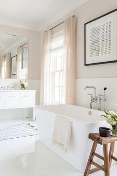 Romantic white and pink bathroom is equipped with a rustic saddle stool placed on white porcelain floor tiles beside a rectangular freestanding bathtub paired with a polished floor mount tub filler mounted beneath an abstract art piece hung from a pale pink upper wall.