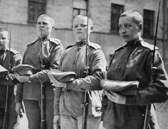 WOMEN ARMED FORCES DURING FIRST WORLD WAR RUSSIA (Q 106252)   Four young Russian female soldiers stand to attention. They are part of the women's 'Battalion of Death', created by the Provisional Government in 1917 in Petrograd (St Petersburg). All have their heads shaved and are holding a shorter cavalry version of the standard Russian service Mosin-Nagant rifle with bayonets fixed.