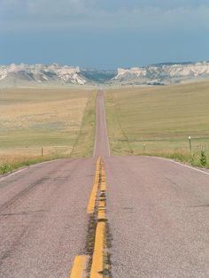 The open road of Wyoming with the badlands of South Dakota in the background.