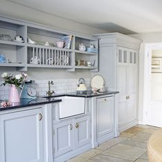 Pale blue country fitted kitchen with white ceramic sink, open shelving and stone tiles on floor.
