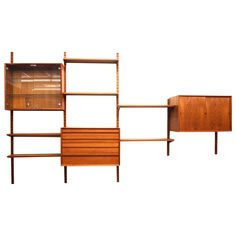 Danish Mid-Century Modern Four Bay Teak Wall Unit in the Style of Cado | From a unique collection of antique and modern cabinets at https://www.1stdibs.com/furniture/storage-case-pieces/cabinets/