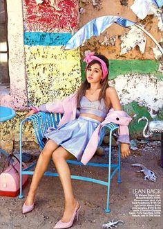 Ariana Grande numa sessão de fotos com uma roupa diferente e original numa espécie de banco de jardim