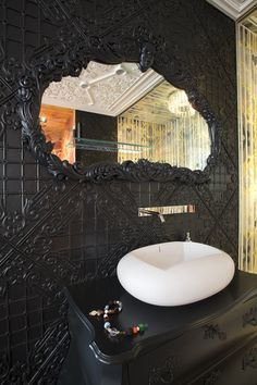Unique mirror that looks like it is being enveloped by the wall / backsplash!  Marcel Wanders-Private Residence
