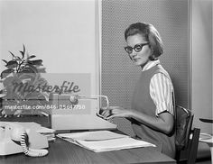 1960s SECRETARY TYPIST WEARING STYLISH EYEGLASSES USING MANUAL TYPEWRITER AT DESK