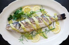 Whole grilled branzino fish, or European seabass, served with a rosemary vinaigrette sauce.