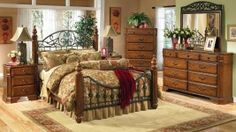 "With beautiful scrolling metal and a rich brown stained finish, the early American country style of the ""Wyatt"" bedroom collection creates a warm relaxing atmosphere for your bedroom decor. The medium brown cherry stained finish is perfectly complemented with the antique bronze color of the scrolling metal crown and traditional styled hardware. #dfwfurniture"