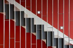 metal stairway in charcoal with wood steps & risers against a red wall, silver graphic detail & step lights