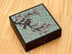 Caixa organizadora para jóias. Tampa com mosaico de pastilhas de vidro. Acabamento externo com pátina preta. Revestimento interno com flocado preto. Nove divisórias. Pode ser feita em outras cores. R$ 135,00