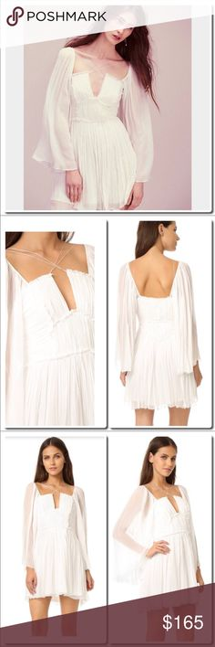 Free People Aquarius Mini Dress in Ivory Celebrate the Age of Aquarius in this ethereal mini dress with a slight fit and flare silhouette and crinkled fabrication. Dramatic flared sleeves add a retro-inspired touch. Delicate crisscross back. Hidden side zipper closure. Lined.  100% Viscose Dry Clean Only Free People Dresses