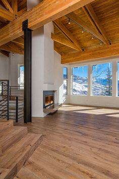 Expansive living room in a private residence in Vail, CO features European Oak wide-plank engineered wood floor, wire-brushed with a custom finish. The ceiling is Reclaimed Spruce. Wood floor and exposed ceiling beams provided and installed by Arrigoni Woods.