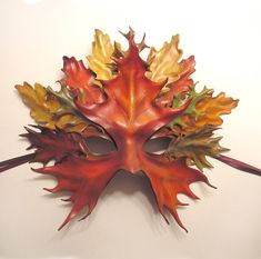 Leaf Mask is made of hand molded and formed leather and has been colored with both leather dyes and acrylic paints. It has a protective topcoat and a pair of coordinating ribbon ties. Mask is const...