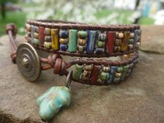 two-wrap bracelet made from 9 X 4 picasso aged matte bugles and 6/0 matte opaque aged striped picasso beads. distressed 2mm leather cord and antique brass button.