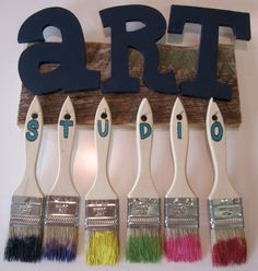 Navy blue A-R-T letters mounted on a 1x4 rough cedar board. Individual chip brushes dipped in bright colored paints, spelling out S-T-U-D-I-O, mounted on finish nails.
