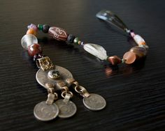 Long Pirate Hair Jewels featuring a Kuchi tribal dangle, ceramic, glass, copper, brass, carved stone, lava stone, pyrite, and wood components by Faire Treasures