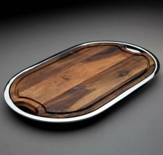 Ridge Tray with Wood Insert by Nambe  A tray as handsome as this one might just steal the spotlight at your next dinner party. Hewn from richly variegated acacia wood and cloaked with a lip of dazzling metal alloy, our Ridge Platter offers two distinct looks in one attractive serving piece. Use it with the wood insert in place, or remove it to reveal a metal underlayer.