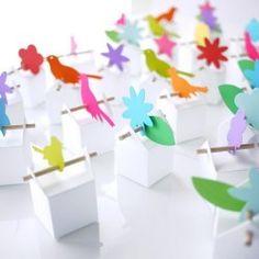 Un jeu de boîtes blanches, bâtonnets et formes multicolores. Les boîtes et étiquettes :desboîtes blanches et desd'étiquettes: oiseaux orange, anis et ros...