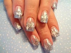 Silver Christmas French tips with snowflakes. Let the snow rain in on your nails by drawing them over your perfect silver glitter French tips.