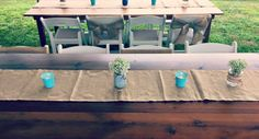 Wooden farm tables with burlap runners and mason jar centerpieces filled with baby's breath.