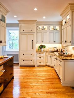 I like the style, the white, the light wood floor, the cabinets running to the ceiling with lighted areas near the top