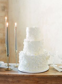 three tiered white fluffy wedding cake with brass taper candle holders