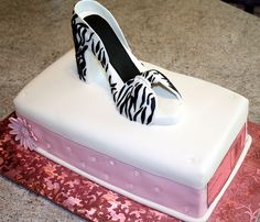 Hatbox cake with a zebra print high heeled shoe. the front of the cake I added a gumpaste pink daisey and also edible sugar diamonds since the girl I made it for loves bling.....on the end of the cake I added an edible image for the label
