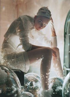 more tim walker..  there is something so enticing about her gaze... and the way the disco balls bounce light beams from underneath her is ethereal