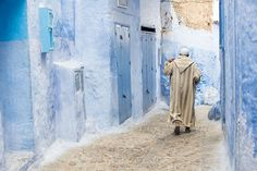 A man in a street of Chefchaouen, Morocco by Bisual Studio