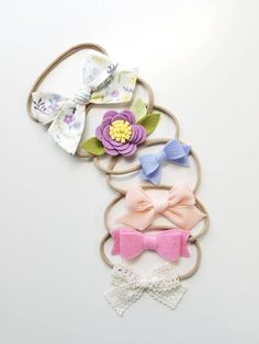 Beautiful Set of 6 Bows in adorable spring colors, Handmade with wool felt and 100% cotton. Your baby girl will be so comfy with them, they will become your go to everywhere bows, You will be amazed with our Signature Nylon band, so soft doesnt leave any marks on your princess. ONE