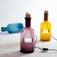 Lampe à poser de coloris ambre composée d'une bouteille en verre et d'un bouchon en bois. Le designer a nommé sa création bouché parce que l'alimentation passe par le bouchon et que pour que la b...