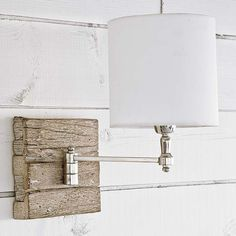 This polished nickel sconce is mounted on a piece of reclaimed wood and topped with a white linen shade. Perfect for the modern farmhouse, boys bathroom, or powder bath. This sconce has a swing arm th