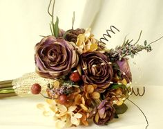 wedding Flowers in Plum and brown silk flowers. An everlasting elegant woodland keepsake! Designed with rustic textures but with a bit of shabby chic for a quirky yet polished style! Woodland Earthtones Plums Brown golden hues, twigs and squiggles. Even a spray of pearls is thrown in along with squiggles, airy twigs. Taking the stage are gorgeous varigated plum brown ranuculus and a silk dried-look muted golden tan mini hydrangea. I set it off with a few pods, woodland leaves and a surprise…