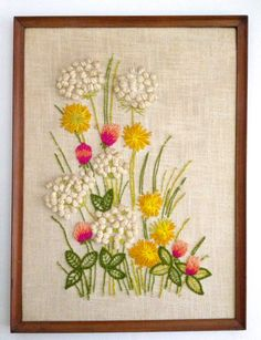 A wonderful mid century framed needlepoint with wildflowers, clovers, daisies and Queen Annes Lace in vibrant colors and gorgeous textures.