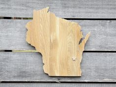 """Wisconsin State Shape Wood Cutout Sign Wall Art in Oak. 17"""" tall. 6 Stain Colors. Personalized with Choice of Wooden Dimensional Heart or Star at Hometown Location. State Your Love for Wisconsin with this state shaped wood cutout sign. Handcrafted from repurposed Oak flooring and finished in your choice of 6 stain colors protected by a polyurethane top coat. Shown in Driftwood stain. ¾"""" deep x 16"""" wide x 17"""" tall at longest points on the shape. Choice of Heart or Star embellishment at…"""