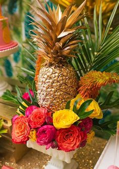 Glam up a pineapple with a simple coat of gold spay paint and surround it with some vibrant florals for a show stopping centerpiece.