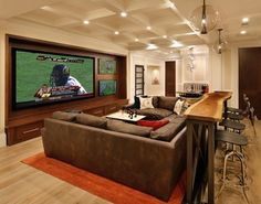 Man cave. Love the table and bar stools behind the couch!