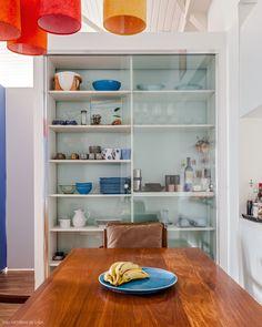 Essa sala de jantar conta com cristaleira com portas de vidro para exibir as louças.