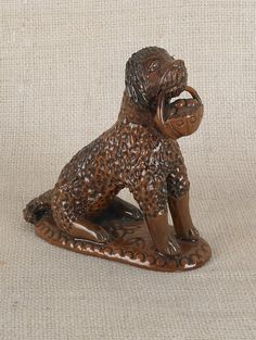 Sold For $ 10,000                                                          Pennsylvania redware seated dog, 19th c., clutching a basket of fruit, 5 1/2'' h.                            Condition report           Overall excellent condition, crack to basket handle, probably in the firing
