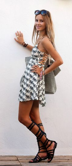 Daisy Ricks is wearing a palm print dress from Missguided, bag from Rip Curl and gladiator shoes from Steve Madden