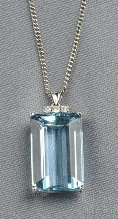 18kt White Gold, Aquamarine, and Diamond Pendant, set with an emerald-cut aquamarine measuring approx. 22.00 x 14.90 x 9.30 mm, full-cut diamond melee accents, suspended from a 14kt white gold curb link chain